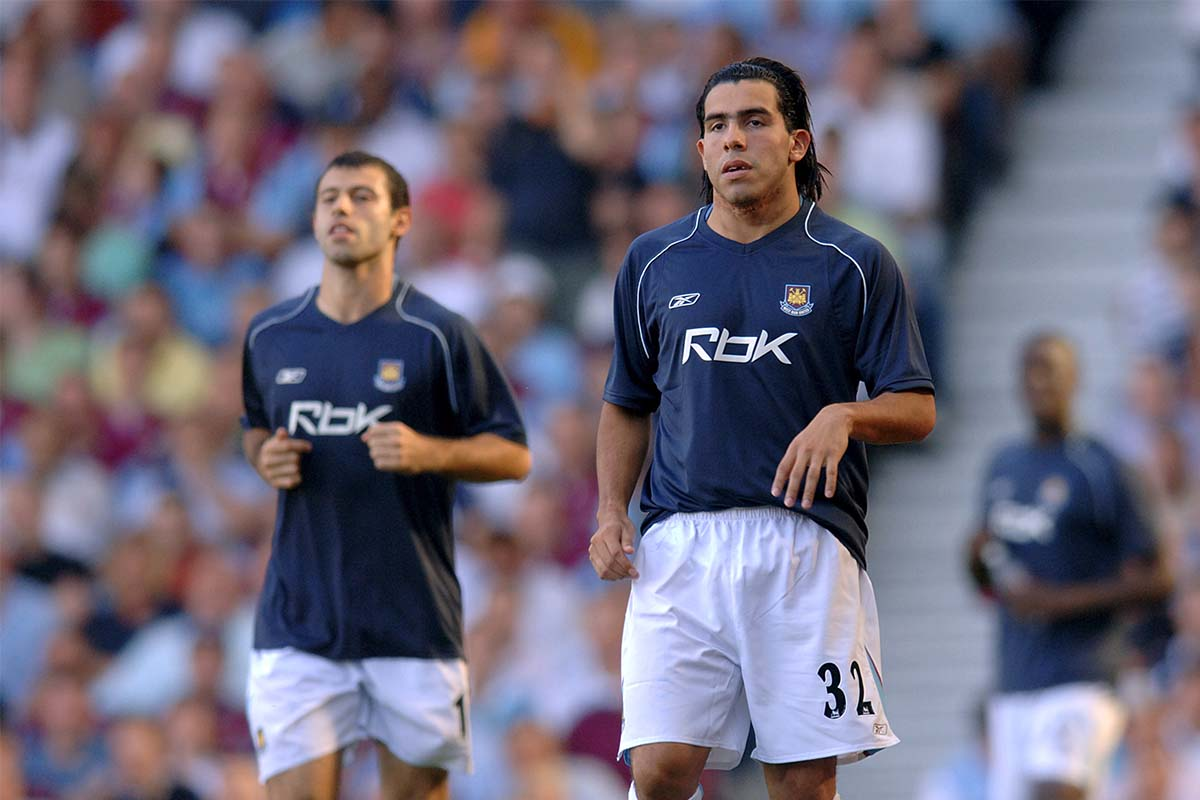 New signings Javier Mascherano and Carlos Tevez of West Ham United warm up on the sidelines