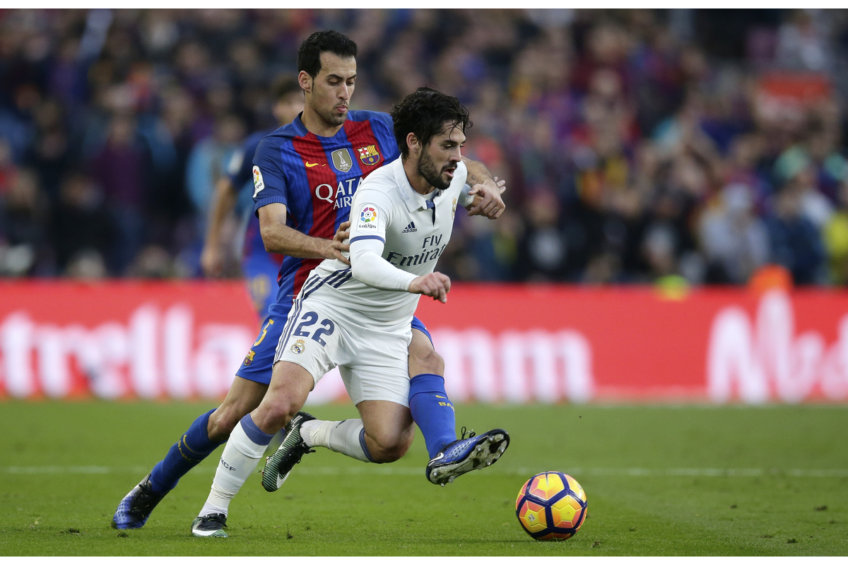 Real Madrid's Isco fights for the ball with Barcelona's Sergio Busquets, left, during the Spanish La Liga soccer match between FC Barcelona and Real Madrid at the Camp Nou in Barcelona, Spain, Saturday, Dec. 3, 2016. (AP Photo/Manu Fernandez)