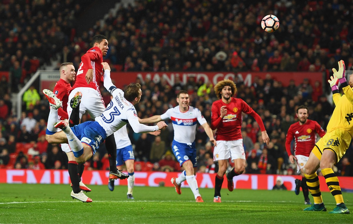 Manchester United centre-back Chris Smalling scores a header against Wigan